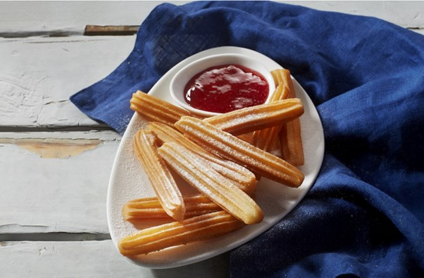 Churros with strawberry sauce and icing sugar